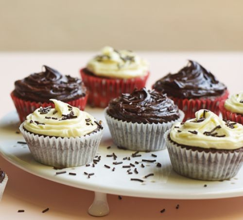 Chocolate cupcakes and white and milk chocolate icing on cake platter with sprinkles