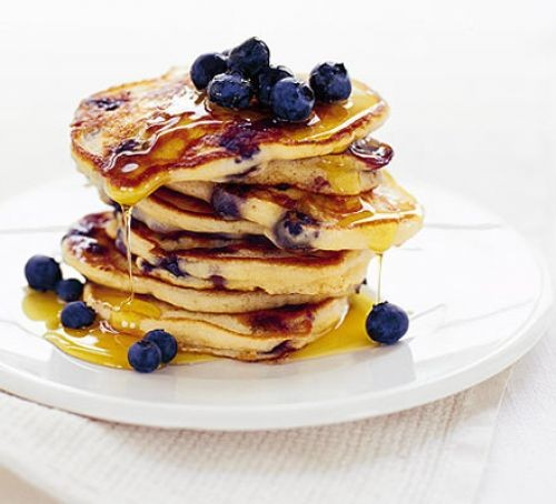 American pancake stack topped with maple syrup and blueberries