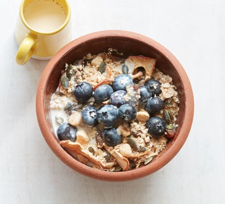 Apricot and hazelnut muesli in a bowl with blueberries on top