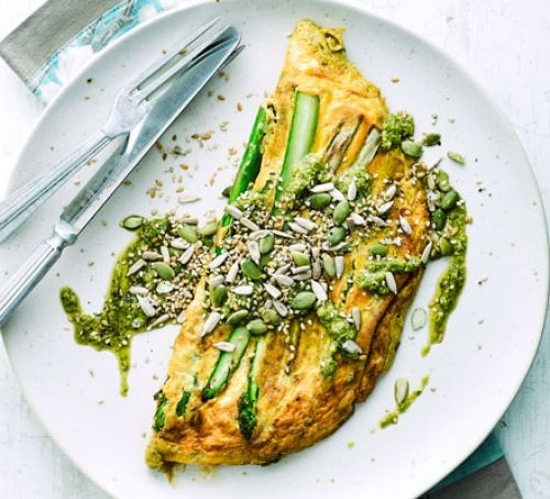 Asparagus stalks in omelette, topped with sprinkled seeds