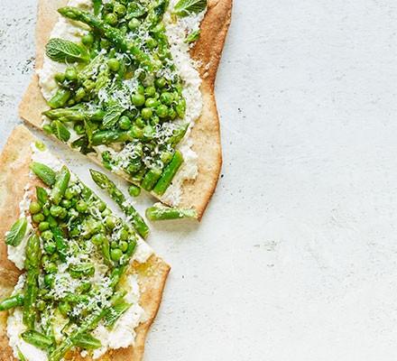 An asparagus, pea & ricotta flatbread cut into two slices