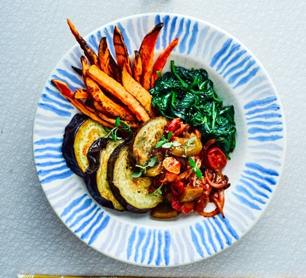 Aubergine goulash with spinach and sweet potato fries in bowl