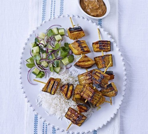 Aubergine skewers with cucumber salad on plate