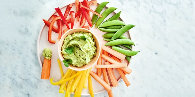 Bowl of hummus surrounded by colourful vegetable crudites