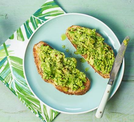 Avocado on sourdough toast with knife on plate