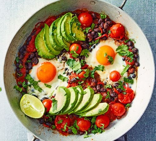 Sliced avocados, black beans and tomatoes with two fried eggs in a bowl