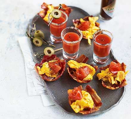 A platter serving Bloody Marys and bacon bowls