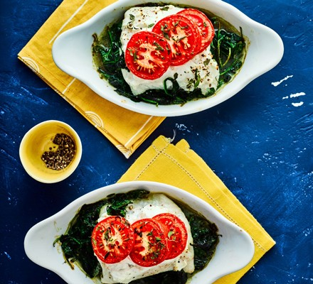 Baked cod with spinach topped with tomatoes in dish