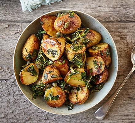 Baked new potatoes with wilted wild garlic served in a bowl
