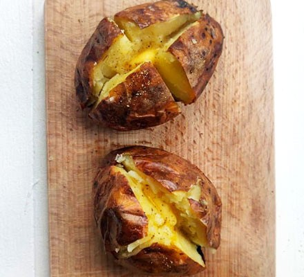 Baked potatoes with butter on board