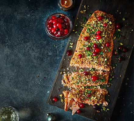 Baked salmon fillet with pickled cranberries, parsley & pistachios cut into slices