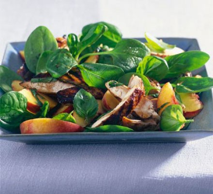 Balsamic chicken & peach salad topped with spinach leaves