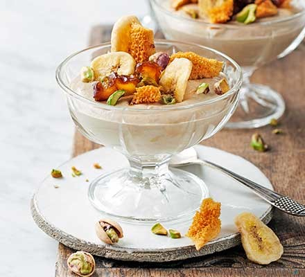 A dessert bowl serving banana custard with dates & honeycomb