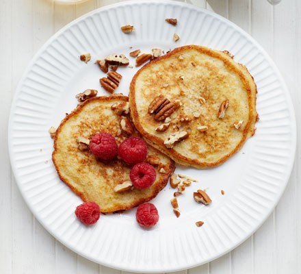 Banana pancakes sprinkled with chopped pecans and raspberries