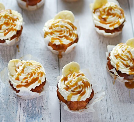 Muffins topped with cream and caramel with banana chips on table