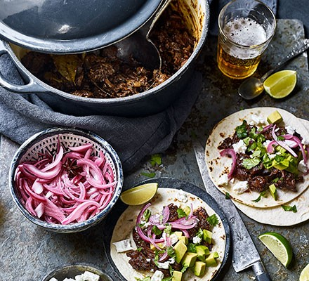 Barbacoa pulled-beef tacos with ingredients alongside