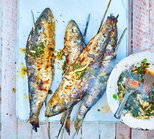 Skewered barbecue sardines on a board by a plate of chermoula sauce