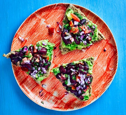 Avocado and black bean triangles topped with onion and tomato on plate