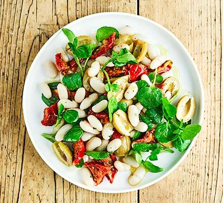 A bowl serving bean, tomato & watercress salad