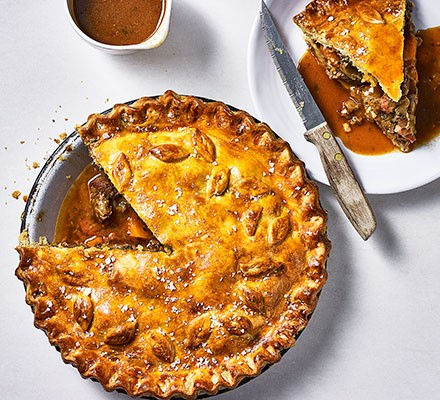 Steak & ale pie served in a pie dish with a slice cut out