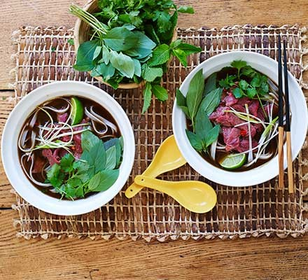 Two bowls of beef pho garnished with coriander