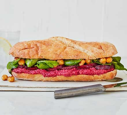 A beetroot, hummus & crispy chickpea sandwich with a knife alongside