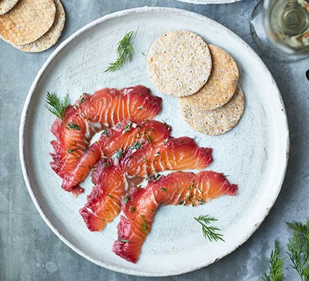 Beetroot & blackberry cured salmon served on a plate with dill and sourdough crackers