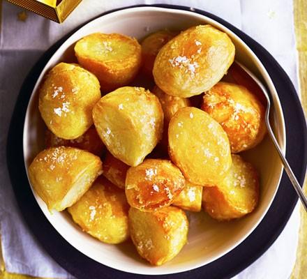 A bowl of crispy roast potatoes sprinkled with salt