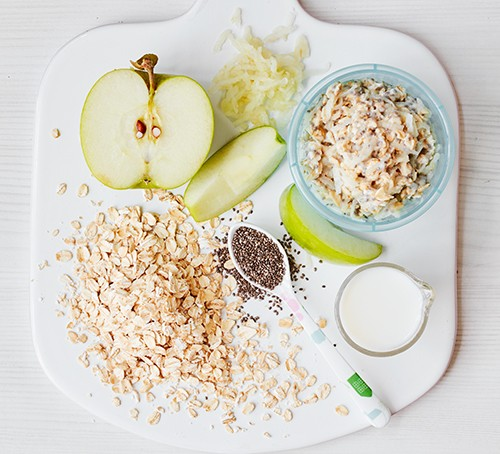 A chopping board with an apple, oats and a bowl of baby Bircher