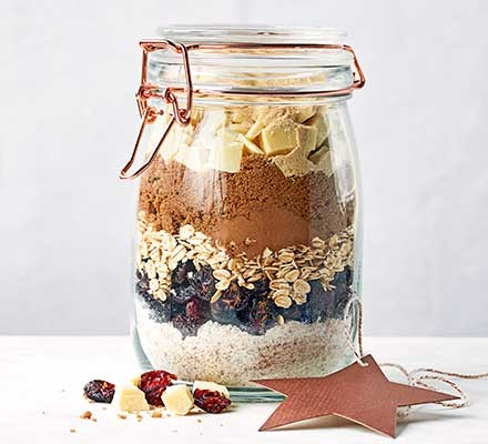 A jar with layers of ingredients for making Christmas biscuits