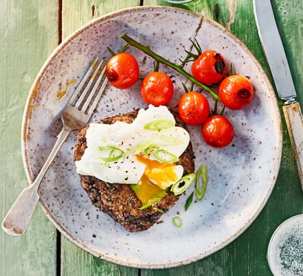 A plate of black bean & barley cakes with a poached egg and tomatoes and