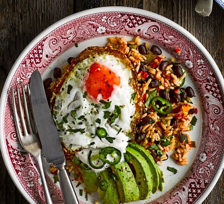 Fried egg with rice and avocado on plate