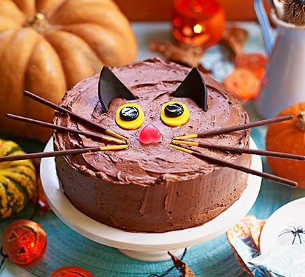 Black cat cake served on a cake stand