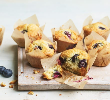 Blueberry muffins on board with berries