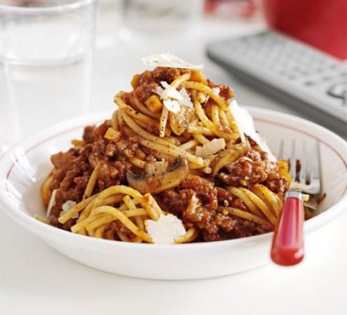 Bowl of spaghetti Bolognese with parmesan cheese and fork