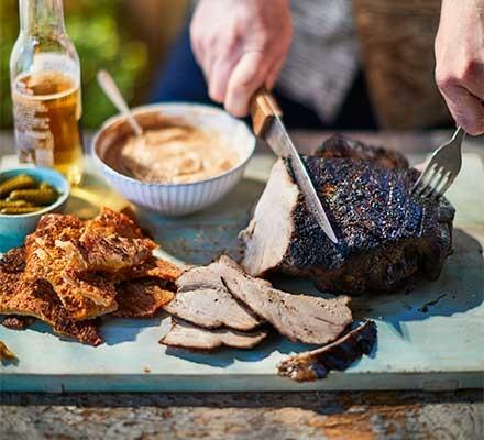 A carving board serving barbecued pork shoulder with cider ketchup