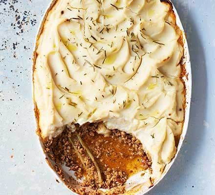 Braised pork cottage pie with celeriac topping served in a casserole dish