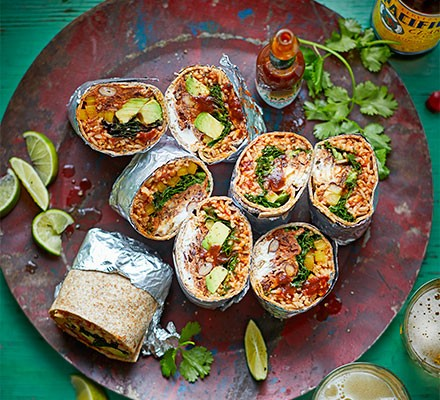 Burritos stuffed with tomato rice served, sliced, on a platter