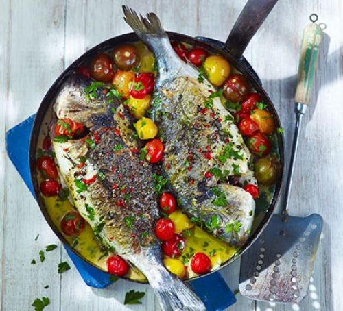 Two sea bream in a pan with yellow and red tomatoes