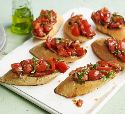 Tomato bruschetta on board with olive oil