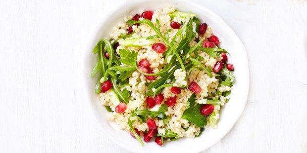 Bulghar wheat, pomegranate seeds and rocket salad in a bowl