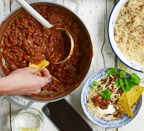 Chilli with tortillas and toppings in bowls
