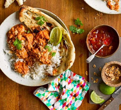 Chicken curry with rice, naan bread and dips on a table