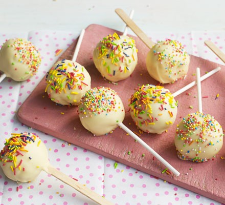 White chocolate cake pops with sprinkles on board