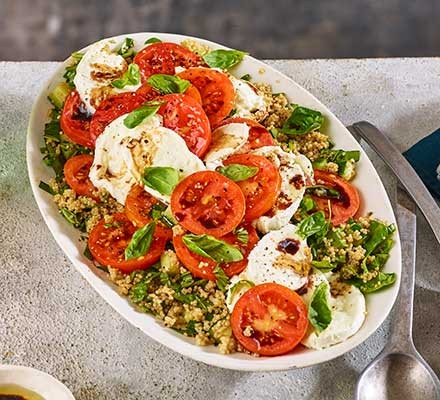 Caprese salad with quinoa served on an oval plate