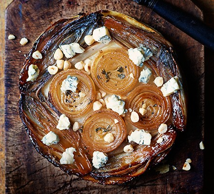 Caramelised onion & chicory tart with gorgonzola on a wooden board