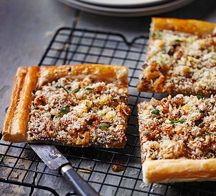 Sliced caramelised onion and cheese puff pastry tart