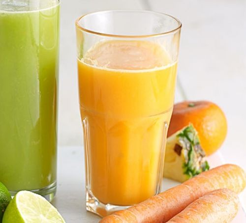 A glass of carrot, clementine and pineapple juice with veg on the side
