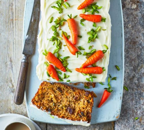 Carrot loaf cake with white frosting and carrot icing pattern