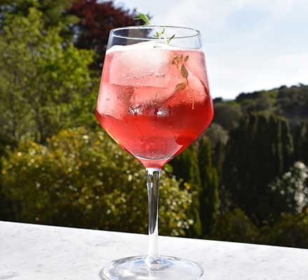 Cassis spritz served in a large glass with thyme to garnish